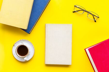 workplace with books, glasses, coffee on yellow background flatlay Imagens
