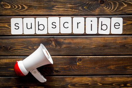Announcement for subscribe with megaphone and text on wooden background top view Archivio Fotografico - 128870378