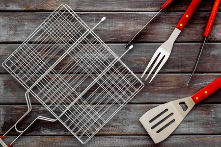 Grid, tongs, fork, spatula for barbecue and grill on wooden background top view