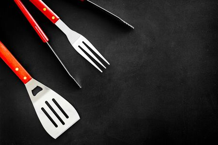 Tongs, fork, spatula for barbecue and grill on black background top view copyspace