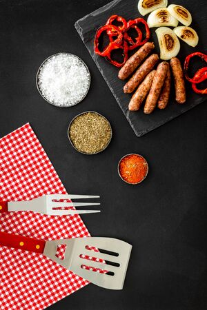 Barbecue with sausages, vegetables on kitchen board and spices on black background top view