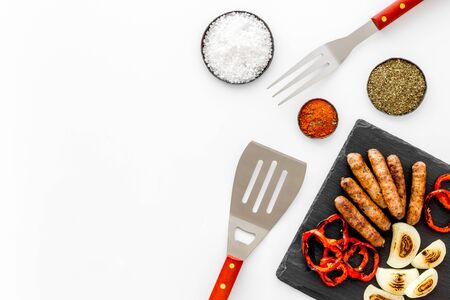 Grilled sausages, vegetables on kitchen board and spices on white background top view mock-up