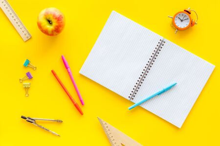 Students desk with stationery, apple, alarm clock, textbook on yellow background top view Imagens