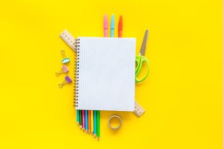 Student accessories, notebook, stationery on pupils desk yellow background top view mock up Imagens
