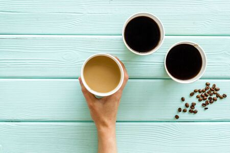 Coffee to take away in paper cups in hands with beans on mint green wooden table background top view