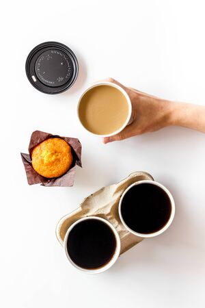 Breakfast with muffin and coffee to-go on white background top view