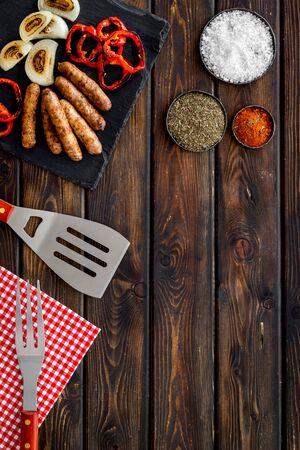 Grilled sausages, vegetables on kitchen board and spices on wooden background top view mock-up
