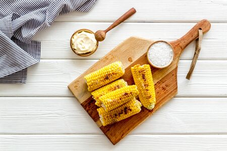 Fried corn on board with salt and butter on white wooden background top view