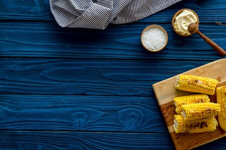 Grilled corn with salt and butter as farm food on blue wooden background top view space for text
