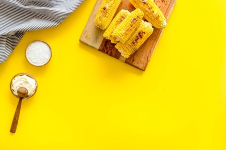 Fried corn on board with salt and butter on yellow background top view mockup Imagens