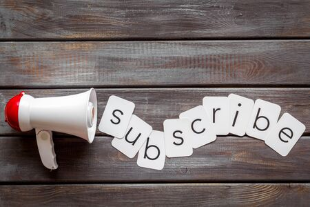 Announcement for subscribe with megaphone and text on wooden background top view Foto de archivo