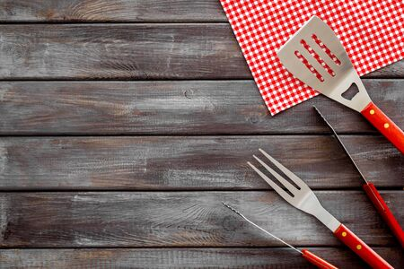 Tongs, fork, spatula for barbecue and grill on wooden background top view space for text