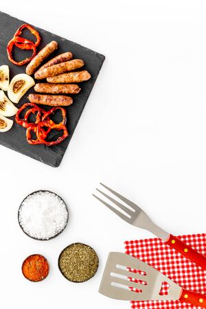 Barbecue with sausages, vegetables on kitchen board and spices on white background top view space for text Фото со стока