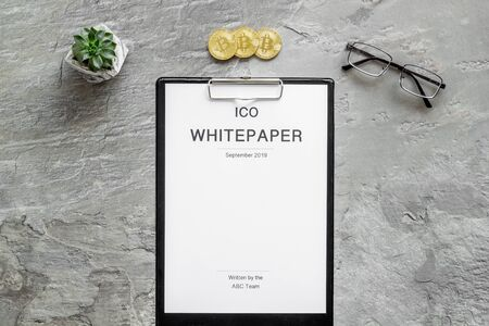 Initial coin offering ICO white paper on gray textured background top view