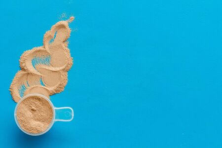 Nutrition for workout with protein cocktail powder on blue background top view mockup Imagens - 128892284