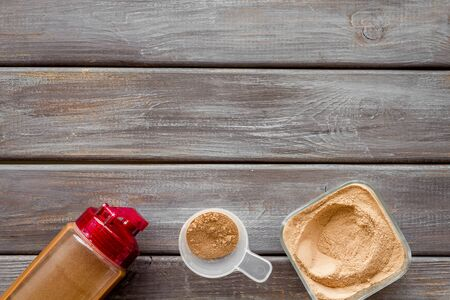 Protein powder and shaker for sport diet on wooden background top view copyspace