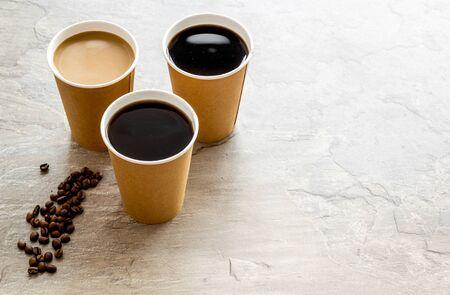 Vasos de papel con café negro y capuchino para llevar, frijoles sobre fondo gris simulacro