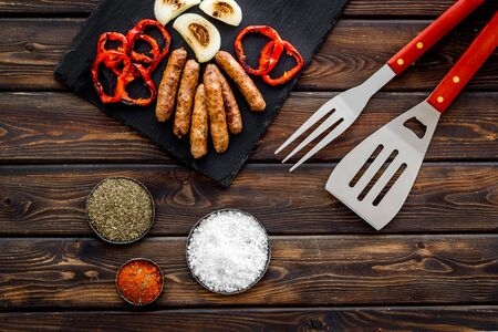 Barbecue with sausages, vegetables on kitchen board and spices on wooden background top view Фото со стока