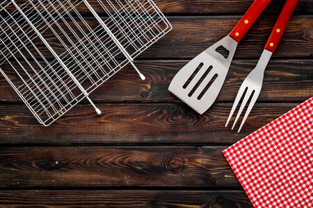Grid, fork, spatula for barbecue and grill on wooden background top view
