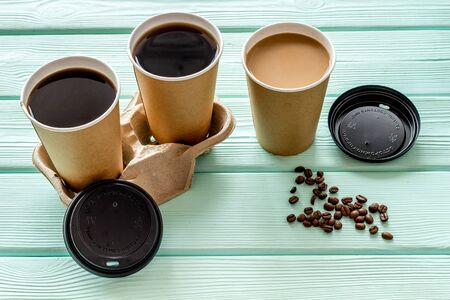 Coffee to take away in paper cups with lids and beans on mint green wooden table background