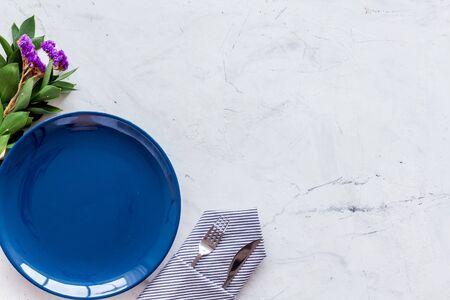 Blauer Teller und Blumen für Tischdekoration auf Marmorhintergrund Draufsicht Platz für Text Standard-Bild