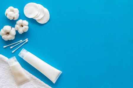 Hygiene cotton swabs, pads and cream for pattern on blue background top view mockup