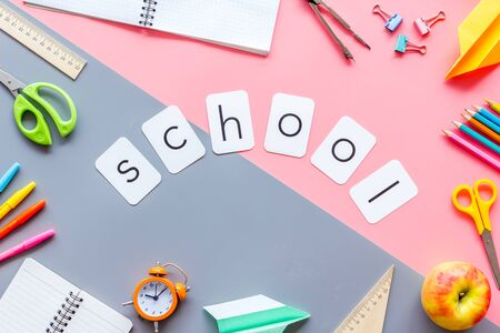School copy with student accessories, notebook, clock on pink and gray background top view
