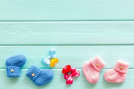 Cute baby clothes for girl and boy with dummy on mint green wooden background top view copyspace
