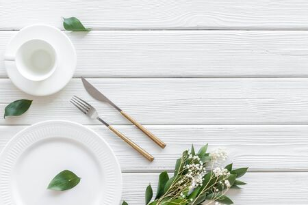 White plates and flowers for table setting on white wooden background top view mockup