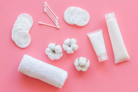 Hygiene cotton swabs, pads and cream for pattern on pink background top view Stock Photo
