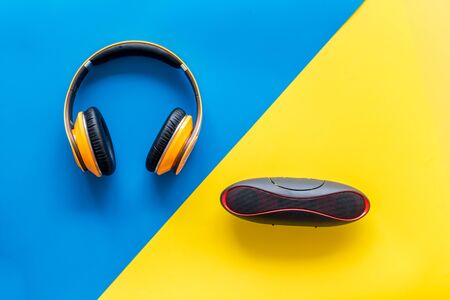 Portable wireless speakers and headphones as gadgets for listen to the music on blue and yellow background top view