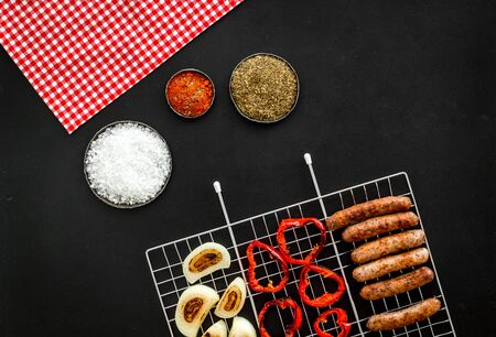Barbecue grid with grilled sausages, vegetables and spices on black background top view Фото со стока