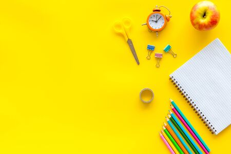 Student accessories, notebook, stationery, clock on pupils desk yellow background top view mock up