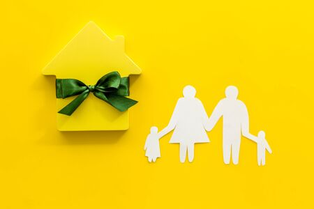 Buying a new house concept with house figure and family on yellow background top view