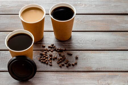 Caution: contents hot. Coffee to take away in paper cups with lids and beans on wooden table background mock up