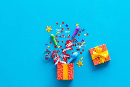 party time concept with decorations in box on blue background top view
