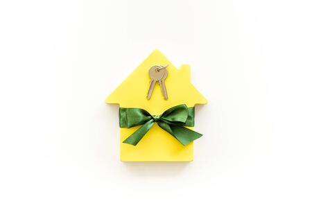 Buying a new house concept with house figure and keys on white background top view Stock Photo