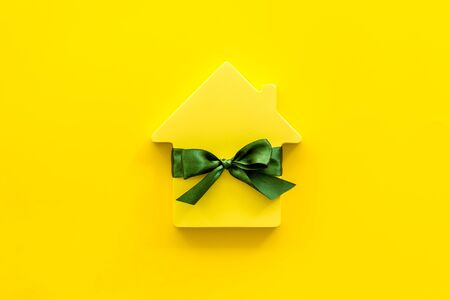 Buying a new house concept with house figure on yellow background top view space for text