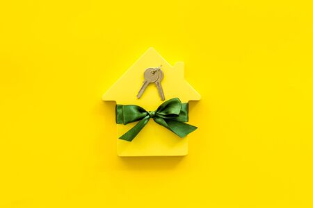 Buying a new house concept with house figure and keys on yellow background top view Stock Photo