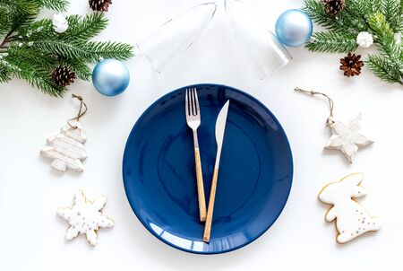 Table setting for new year 2020 celebration with pine branch, decorations, plate and tableware white background top view Фото со стока