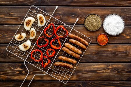 Barbecue with sausages, vegetables on grid and spices on wooden background top view