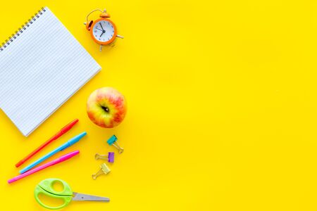 Education mockup with pupils stationery, clock, apple and textbook on yellow background top view Imagens