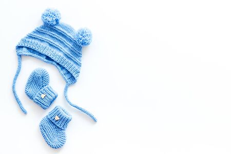 Booties and hat for newborn boy on white background top view mockup
