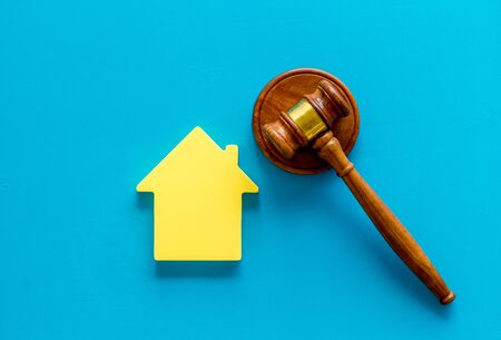 Inscribed gavel, house figure for inheritance concept on blue background top view Banco de Imagens