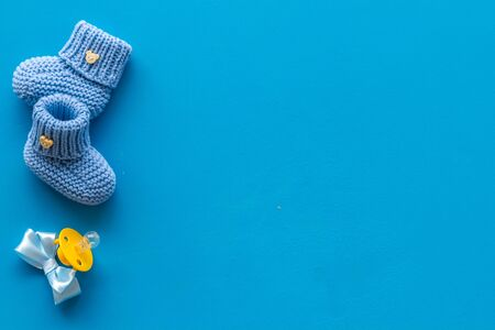 Blue knitted footwear and dummy for baby on blue background top view mockup Stock Photo - 129303952