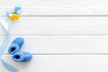 Blue knitted footwear and dummy for baby boy on white wooden background top view mockup Stock Photo - 129305091