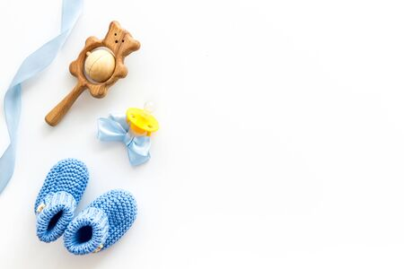 Blue knitted footwear and rattle, dummy for baby on white background top view mockup