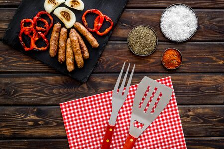 Barbecue with sausages, vegetables on kitchen board and spices on wooden background top view Imagens