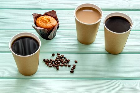 Breakfast with muffin and coffee to-go on mint green wooden background