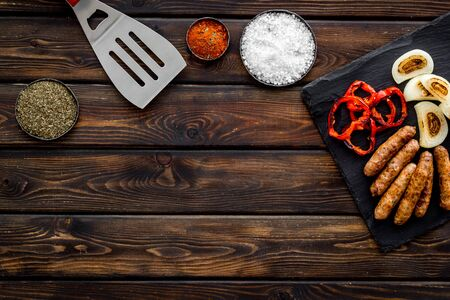 Grilled sausages, vegetables on kitchen board and spices on wooden background top view mockup